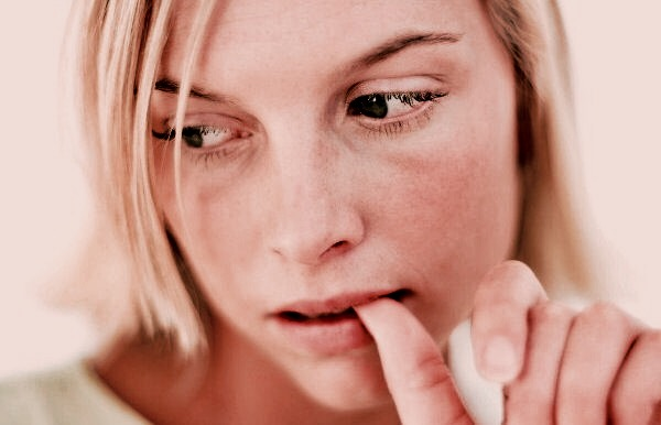 Young Woman Biting Her Finger Nail --- Image by © Royalty-Free/Corbis